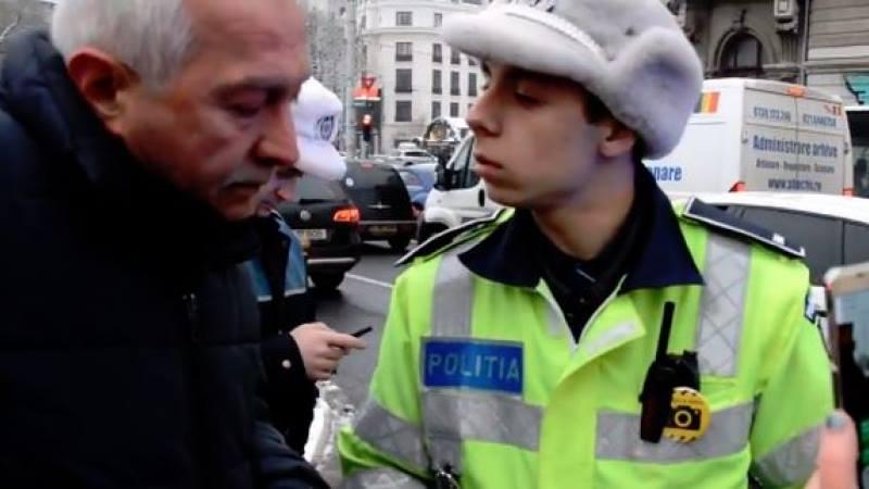 Tânăr milițian amendându-l pe revoluționarul Doru Mărieș când depunea o coroană la Troița de la Universitate