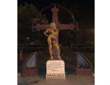 Margherita de la Clejani cocoțată pe crucea troiței Eroilor Revoluției din 1989care şi-au dat viața pentru ca Margherita să fie liberă să-si exprime prostia